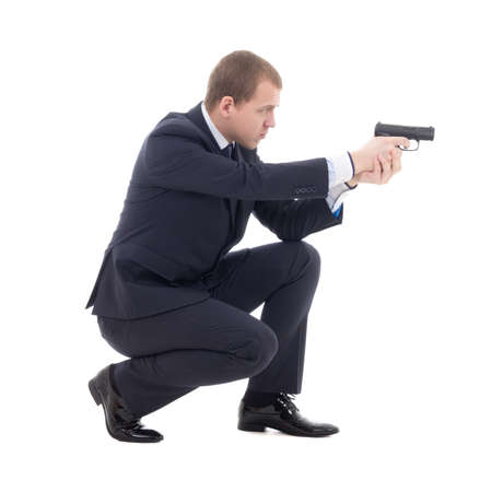 special agent man in business suit sitting and shooting with gun isolated on white background