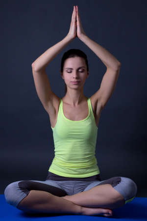 young woman sitting in lotus position over grey background photo