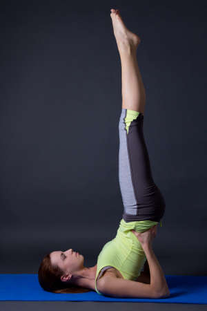 young beautiful sporty girl doing legs up exercise over grey background photo