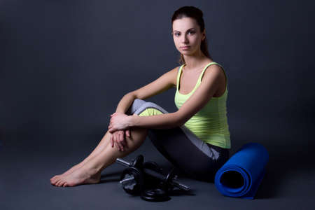 young woman in sports wear with yoga mat and dumbbells over grey background photo
