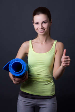 young woman in sports wear posing with yoga mat and thumbs up over grey background photo