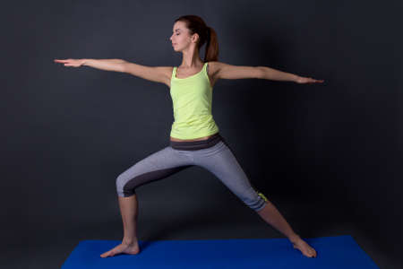 young sporty woman doing yoga over grey background photo