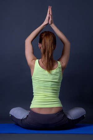 back view of sporty woman sitting in lotus position over grey background photo