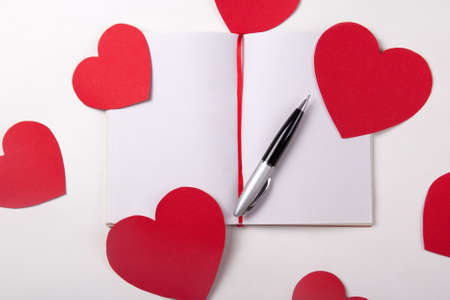 love letter concept - note book, pen and red paper hearts photo