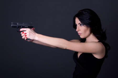 mujer con arma: mujer atractiva joven de tiro con pistola sobre fondo gris
