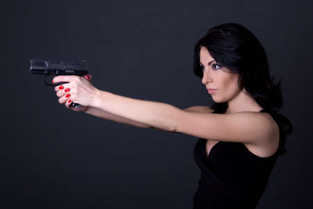 one armed: young sexy woman shooting with gun over grey background Stock Photo