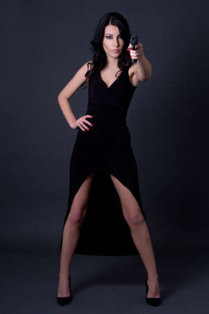 young sexy woman secret agent in black dress posing with gun over grey background