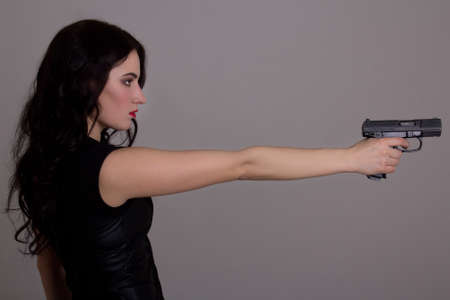 side view of young beautiful woman with gun over grey background