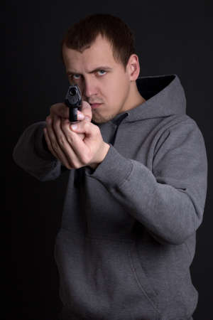 assasin: young man criminal aiming with gun over grey background