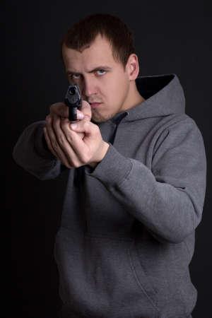 assasin: young man criminal aiming with gun over grey background