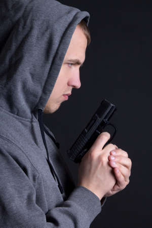 assasin: profile of man criminal with gun over grey background