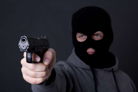 assasin: man in black mask aiming with gun over grey background