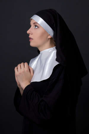 religious habit: religion concept - young woman nun praying over grey background Stock Photo