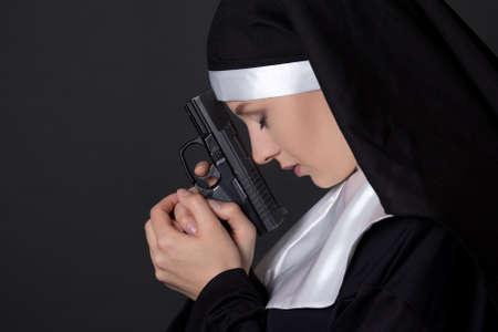 nun: young woman nun praying with gun over grey background
