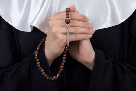 nun: close up of rosary in female nun hands