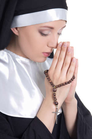 close up portrait of young beautiful woman nun praying with rosary isolated on white background photo
