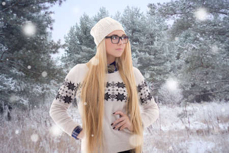 young beautiful woman in winter clothes walking in forest photo