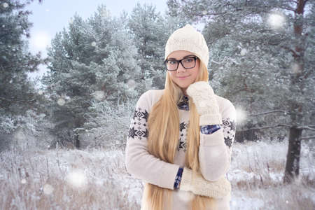 young pretty woman in warm clothes walking in winter park photo