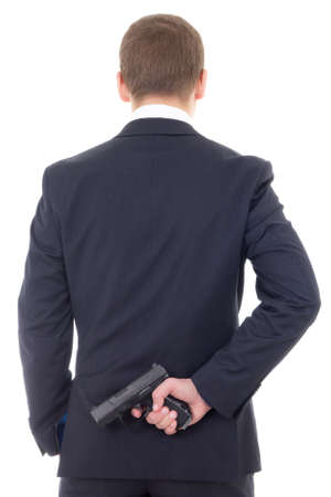 man in business suit hiding gun behind his back isolated on white background