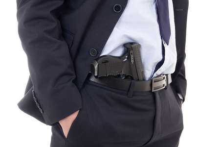 close up of gun in policeman or bodyguard pants isolated on white background photo