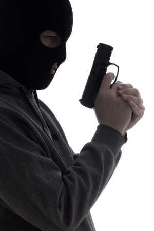 assasin: dark silhouette of burglar or terrorist in mask with gun isolated on white background
