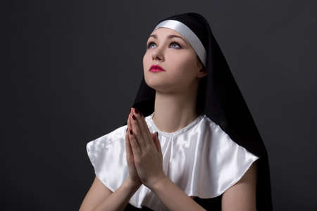 religious habit: beautiful woman nun with red lips praying over grey background