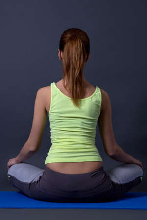 back view of young woman sitting in lotus position over grey background photo