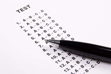 close up of test score sheet paper with answers and metal pen photo