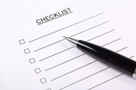 checklist: close up of blank checklist and metal pen