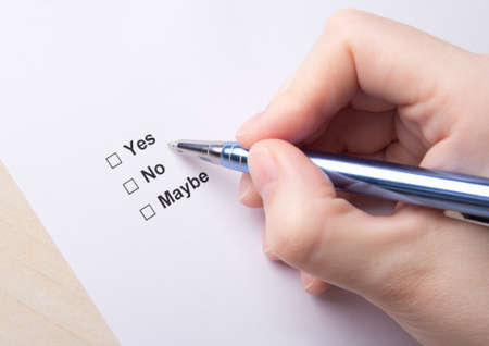 survey: female hand filling survey with yes, no, maybe answers with pen