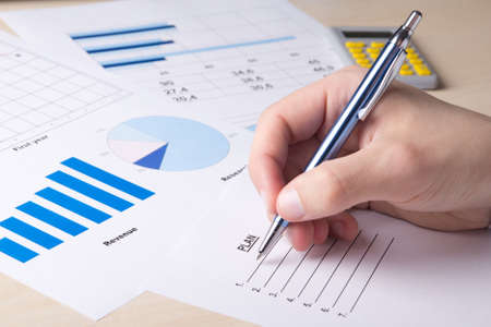 analyzed: business concept - close up of graphs and charts analyzed by businessman