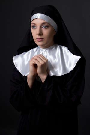 religious habit: religion concept - praying nun over grey background Stock Photo