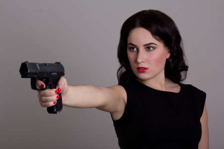 serious woman shooting with gun isolated on white background