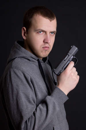 assasin: young man criminal holding gun over grey background