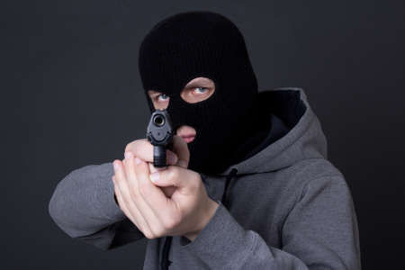 assasin: masked man criminal aiming with gun over grey background