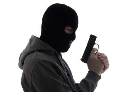 dark silhouette of burglar or terrorist in mask holding gun isolated on white background