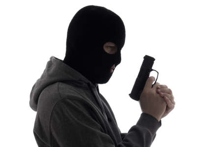 dark silhouette of burglar or terrorist in mask holding gun isolated on white background