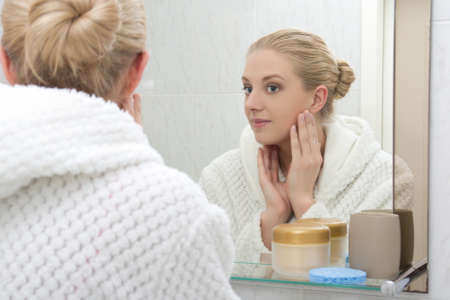 young beautiful woman in bathrobe looking at mirror in bathroom Standard-Bild