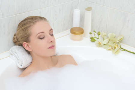 거품 목욕에 편안한 아름 다운 젊은 여자