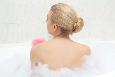 back view of young woman relaxing in bath and washing herself
