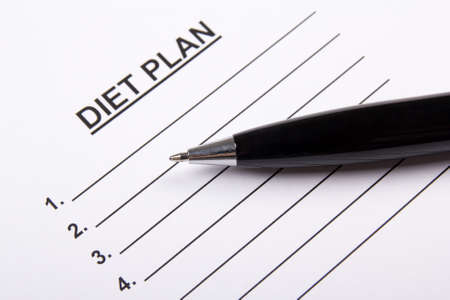 weightloss plan: sheet of paper with diet plan and metal pen Stock Photo