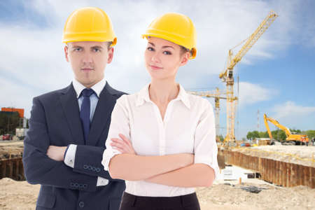 young man and woman in builder s helmets at construction site photo