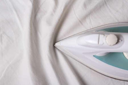 close up of iron ironing wrinkled white cotton linen