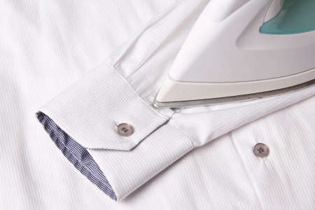 close up of iron ironing sleeve of white cotton shirt Фото со стока