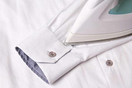 close up of iron ironing sleeve of white cotton shirt Standard-Bild