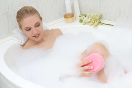 woman laying: young beautiful slim woman bathing with pink sponge