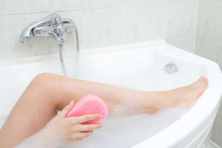 sexy bath: sexy woman washing legs in bath with pink sponge