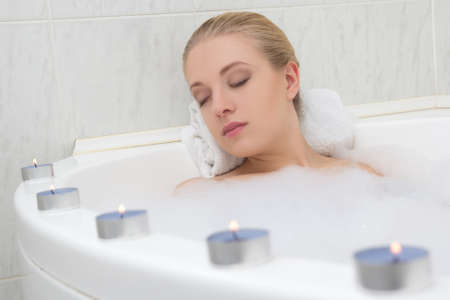 bath: young beautiful woman relaxing in bath with candles Stock Photo