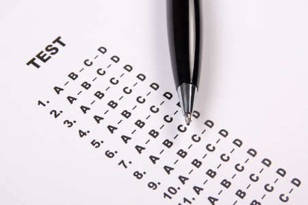 close up of test score sheet with answers and metal pen photo