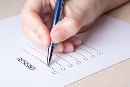 close up of female hand filling checklist with metal pen Stock Photo